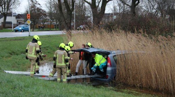 Brandweer helpt vrouw uit auto na ongeluk.